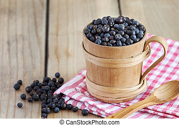 Dried juniper berries in wooden cup. Copy space