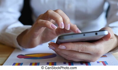 Businesswoman Using Mobile Phone. Stock Charts On Table