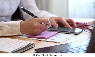 Woman Writes Data On Paper - Woman Hands At Table With Smart...