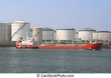 Oil Tanker and Silos - Red oil tanker among oil storage...