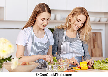 Smiling teenage girl and her mother cooking on the kitchen