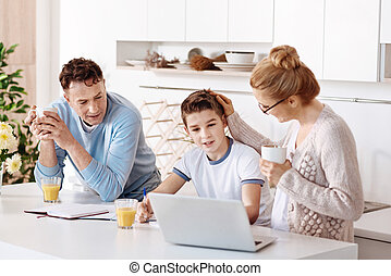 Diligent pupil studying in the kitchen with his parents