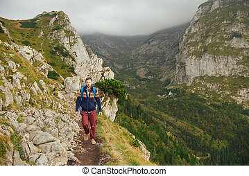 Hiker walking along a trail high up in the mountains