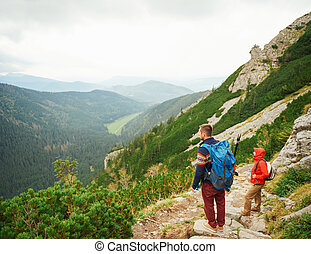 Hikers taking in the view from a rugged mountain trail - Two...