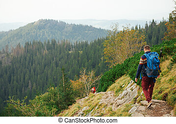 Hikers making their way down a rocky trail in the mountains