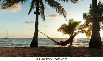 Man Enjoying the Sunrise - Man swinging in a hammock,...