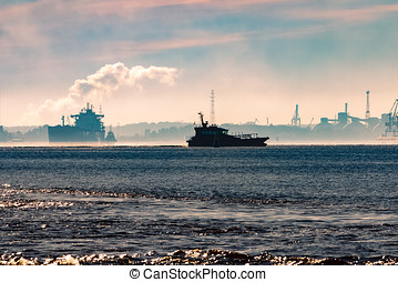 Pilot ship silhouette in the morning against the cargo port