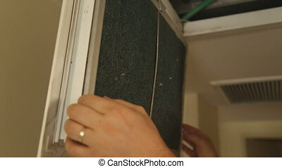 Pulling out dusty AC filter for cleaning - Shot of Pulling...