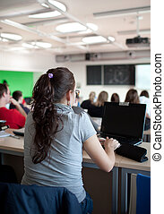 young pretty female college student sitting in a classroom full of students during class