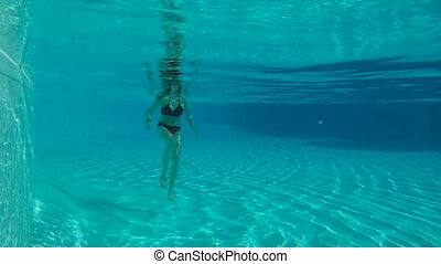 Woman standing underwater in slow motion