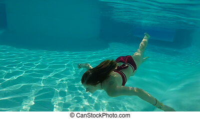 Woman swimming underwater in slow motion - Woman in red...