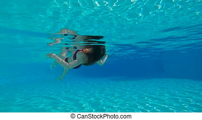 Woman swimming on back underwater in slow motion in swimming...