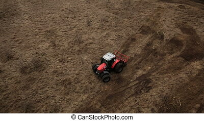 Farmland aerial view with a tractor plowing soil - Swampy...