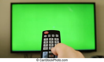 POV holding remote control with green screen inside tv LED...
