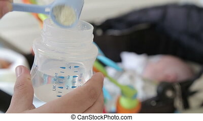 Preparing infant milk formula for a baby - Shot of Preparing...