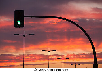 Traffic lights on the road at sunset