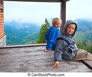 Children on wooden mountain cottage porch - Small boy and...
