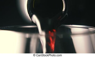 Red wine is poured into a glass, close-up