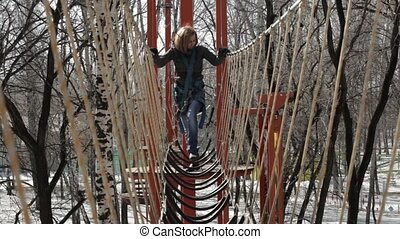 Young female climber walks by pendant rope bridge on high...