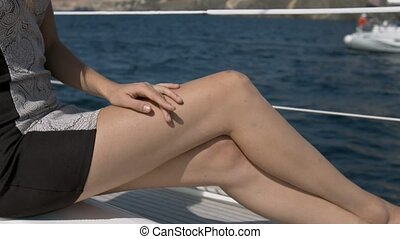 Sexy legs tanning young woman lying in sun on yacht