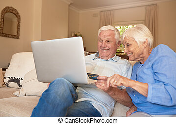 Happy seniors shopping online from their living room sofa