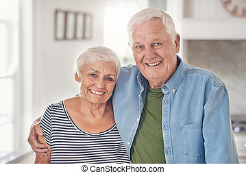 Content senior couple standing together at home in their...