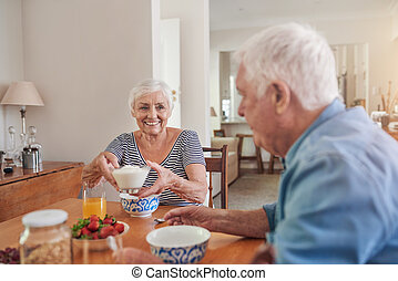 Content seniors eating a healthy breakfast together at home...