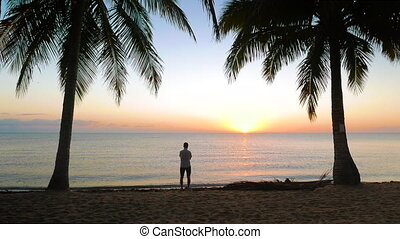 Tranquil Scene of Sun Rising Over the Sea - Man walking in...