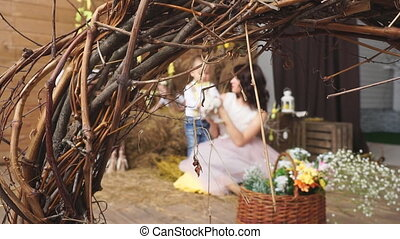 Through the branches in the background, mother and son. Easter photo shoot