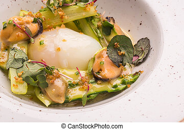 Asparagus with goose egg and sauce in a round plate