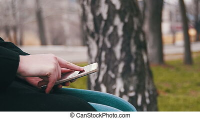 Young Woman using a Smartphone on a Bench in the City Park....