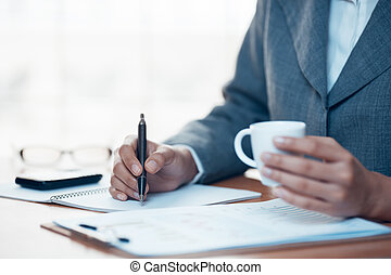 Business person writing report in office