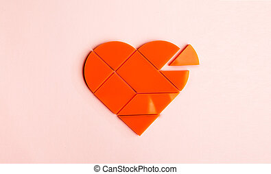 Plastic puzzle in the form of heart with disconnected piece...