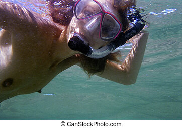 A beautiful young woman goes snorkeling. - A stock...