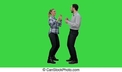 Young couple dancing together on a Green Screen, Chroma Key....