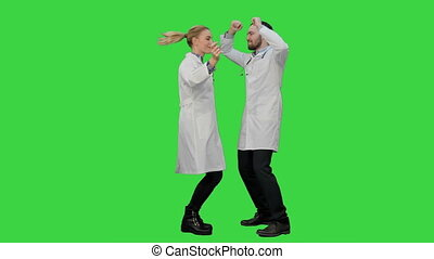 Two funny medical doctors with funny energy dance on a Green Screen, Chroma Key.