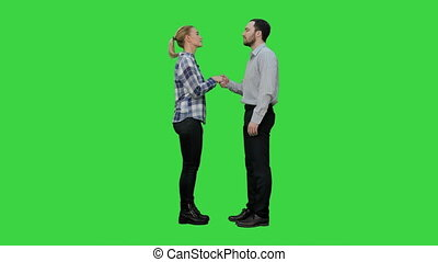 Two young people shake hands keep silent on a Green Screen,...