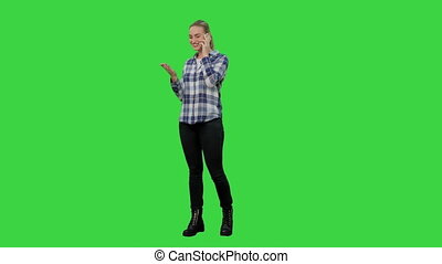 Happy young woman talking on mobile phone smiling on a Green Screen, Chroma Key.