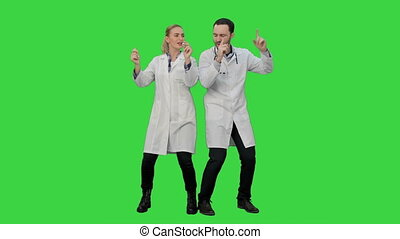 Young doctors in a good mood dancing and singing songs on a...