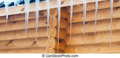 wooden house - icicles hanging from the roof of a wooden...
