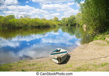 Wooden boat on the river bank - summer landscape. Wooden...