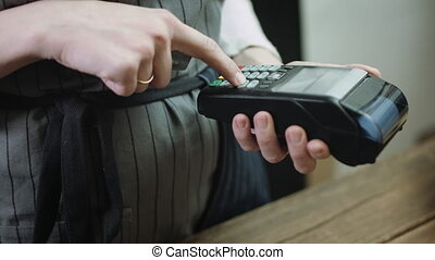 Woman swiping credit card through credit card reader -...