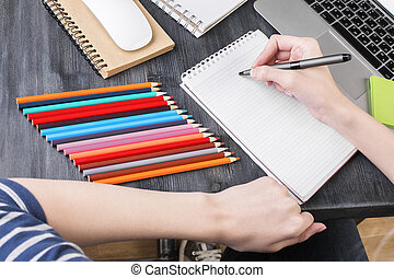 Girl writing in notepad top - Top view of wooden office...
