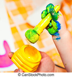 Fingerpaint - Child holding finger paint brush close-up