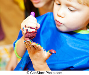 Fingerpaint - Little girl with paint brush making a finger...