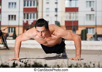 Low angle view of a fit young man doing press-ups on the...
