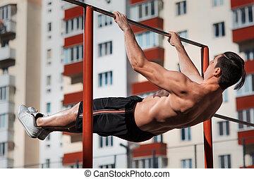 Fit young man doing push ups on horizontal bar outdoors. Man...