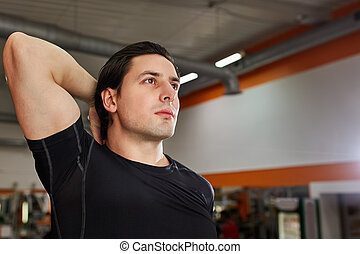 Portrait Of A Athlete Man Measuring His muscles In The Gym