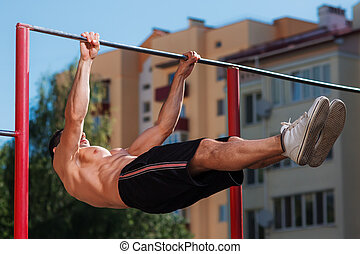 Fitness man doing stomach workouts on horizontal bar...