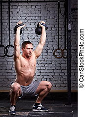Crossfit training. Fitness man in grey shorts doing a weight...